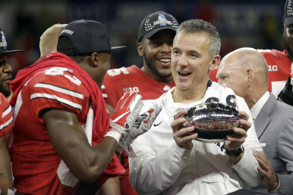 Ohio State head coach Urban Meyer and wide receiver Terry McLaurin, left, celebrate early Sunday after defeating Northwestern 45-24 in the Big Ten championship in Indianapolis. (AP Photo/AJ Mast)