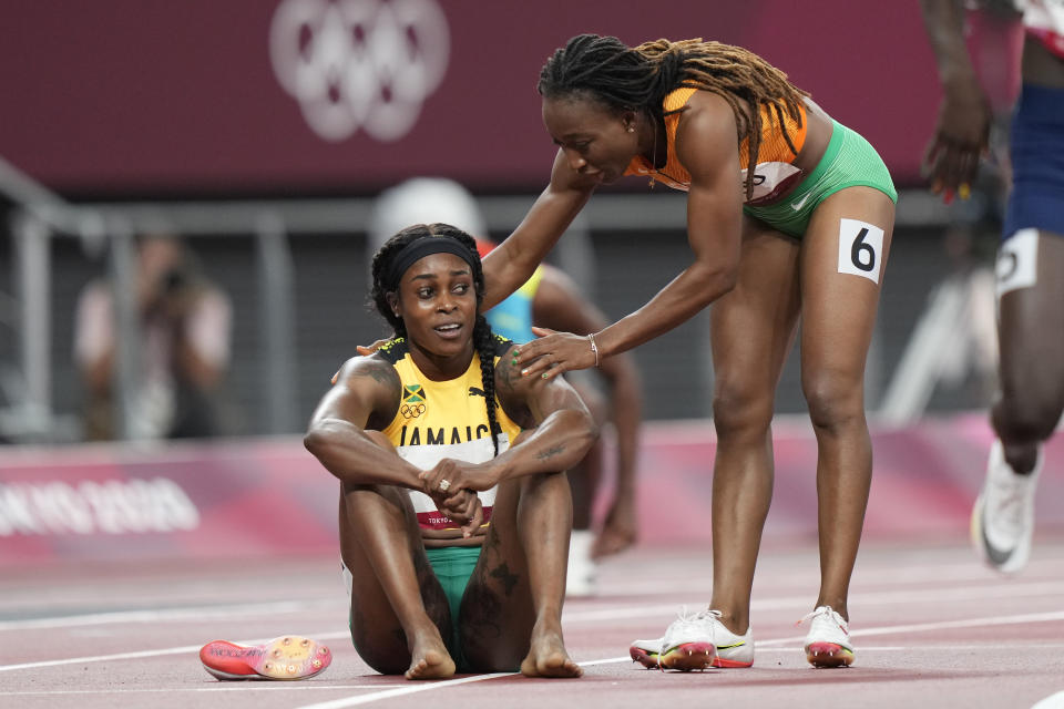 Elaine Thompson-Herah, of Jamaica, is congratulated by Marie-Josee Ta Lou, of Ivory Coast, after winning the final of the women's 200-meters at the 2020 Summer Olympics, Tuesday, Aug. 3, 2021, in Tokyo. (AP Photo/David Goldman)
