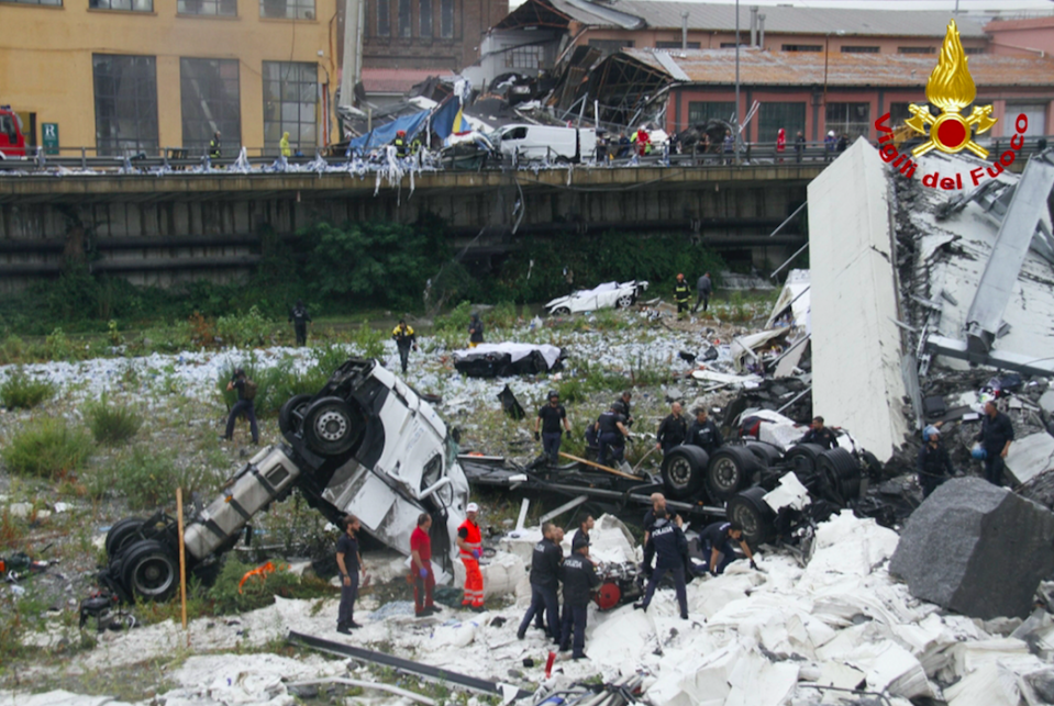 <em>Crushed vehicles lie amongst the concrete and steel following the collapse (AP)</em>