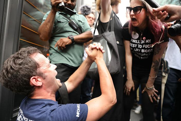 A President Donald Trump supporter (left) argues with anti-Trump protesters as they gather outside of Trump Tower.