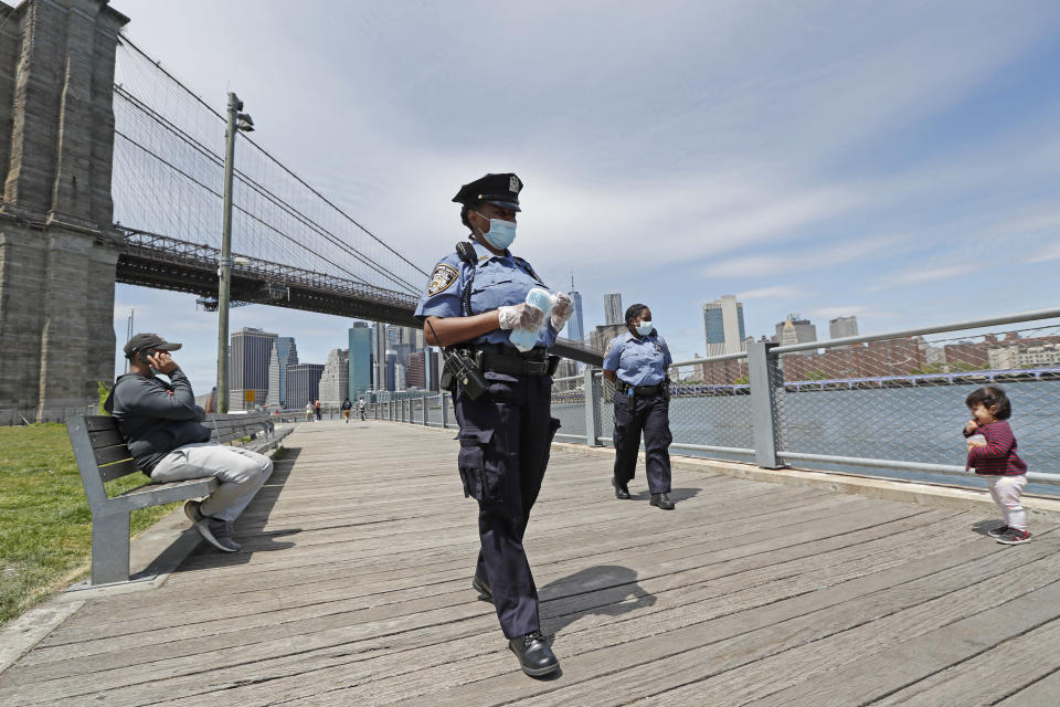 A youngster approaches a team of New York City police officers as they walk with face masks to hand out to anyone who needs or asks for one during the current coronavirus outbreak, Sunday, May 17, 2020, in Brooklyn Bridge Park in New York. (AP Photo/Kathy Willens)