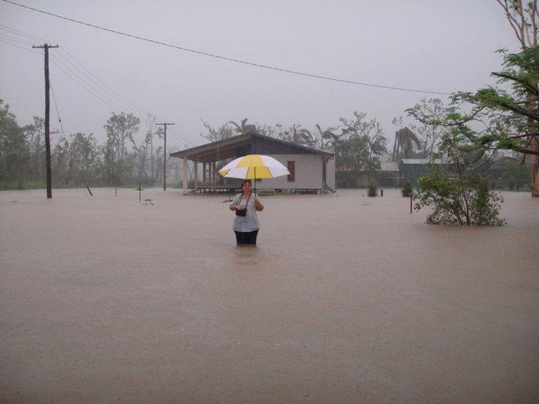 This file photo shows a woman standing in floodwater during heavy rain in Cardwell, in the far north of Australia's Queensland, on March 8, 2011. As floods swept northeastern Australia on Friday after the remnants of tropical cyclone Oswald dumped huge rains around the coastal city of Rockhampton, authorities have reported 20 water rescue cases, plucking people from stranded cars and homes