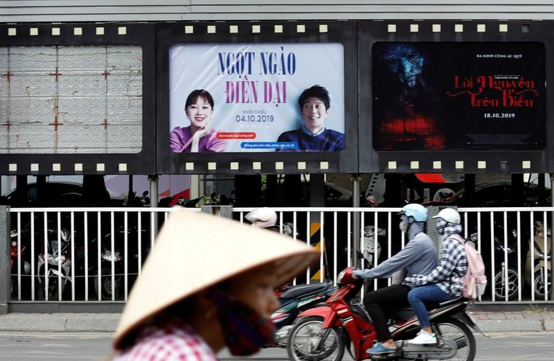 "FILE PHOTO: Bikers go past an empty space where a promotional poster for the DreamWorks film ""Abominable"" stood before being taken down at a cinema in Hanoi"