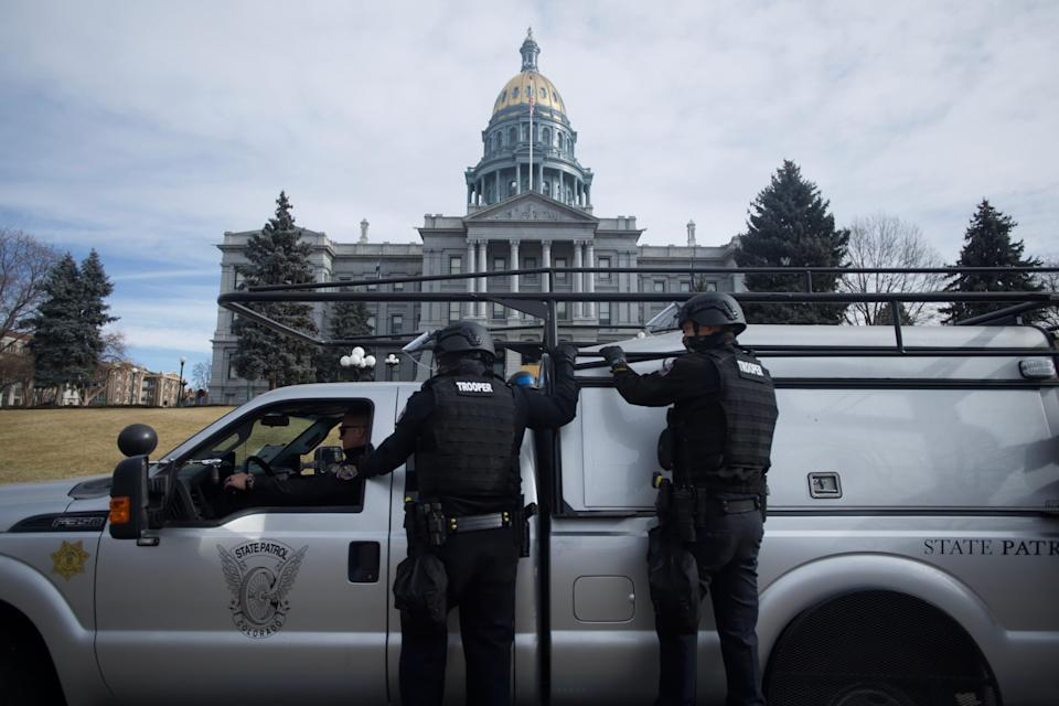 Members of law enforcement hang onto a vehicle as it drives in front of the Colorado Capitol building in preparation for anticipated protests in Denver, Colo., on Sunday, Jan. 17, 2020.