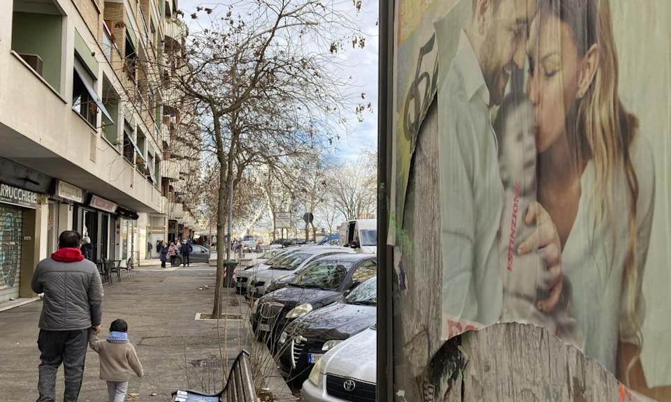 A poster in Rome showing a couple with a baby has 'extinction' written across it.
