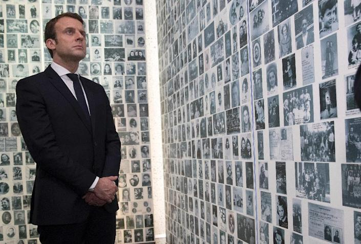 Presidential candidate Emmanuel Macron looks at some of the 2,500 photographs of young Jews deported from France during WWII, as he visits the Shoah Memorial in Paris (AFP Photo/PHILIPPE WOJAZER)