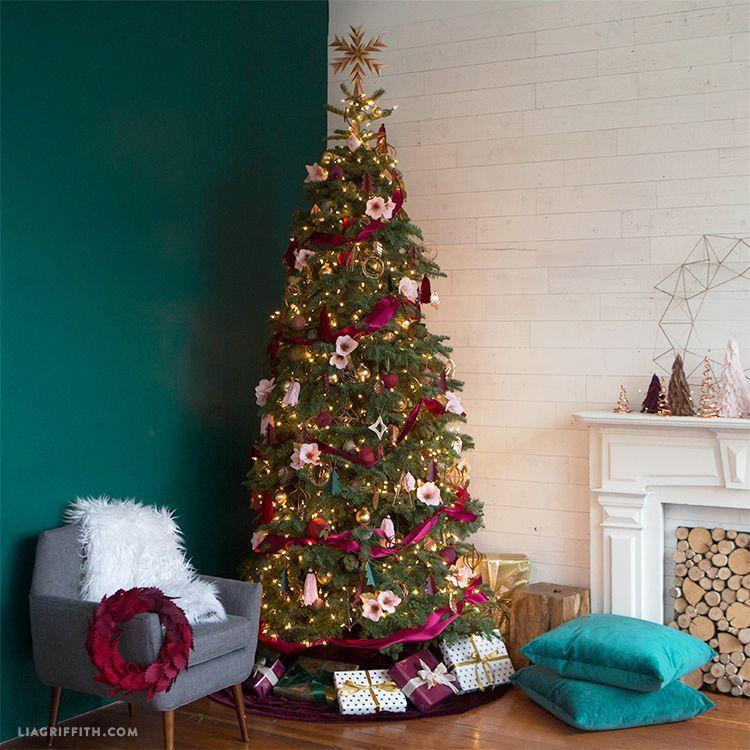 """<p>Take a more classic — yet still unique — approach to decorating your tree this year. Instead of red and green ornaments, use pink, plum, and burgundy ones. But make sure you set aside a whole day for this one, it'll take some time to craft the tree decorations.</p><p><strong><em>Get the tutorial at <a href=""""https://go.redirectingat.com?id=74968X1596630&url=https%3A%2F%2Fliagriffith.com%2Fjewel-toned-metallic-christmas-tree%2F&sref=https%3A%2F%2Fwww.womansday.com%2Fhome%2Fhow-to%2Fg2025%2Fchristmas-tree-decorations%2F"""" rel=""""nofollow noopener"""" target=""""_blank"""" data-ylk=""""slk:Lia Griffith"""" class=""""link rapid-noclick-resp"""">Lia Griffith</a>.</em></strong></p><p><a class=""""link rapid-noclick-resp"""" href=""""https://www.amazon.com/VATIN-Burgundy-Polyester-Wrapping-Wedding/dp/B0836QPPL6?tag=syn-yahoo-20&ascsubtag=%5Bartid%7C10070.g.2025%5Bsrc%7Cyahoo-us"""" rel=""""nofollow noopener"""" target=""""_blank"""" data-ylk=""""slk:BUY BURGUNDY RIBBON"""">BUY BURGUNDY RIBBON</a></p>"""