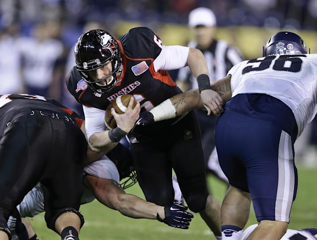 Northern Illinois quarterback Jordan Lynch plows through the Utah State defense for first down during the first half of the Poinsettia Bowl NCAA college football game Thursday, Dec. 26, 2013, in San Diego. (AP Photo/Lenny Ignelzi)