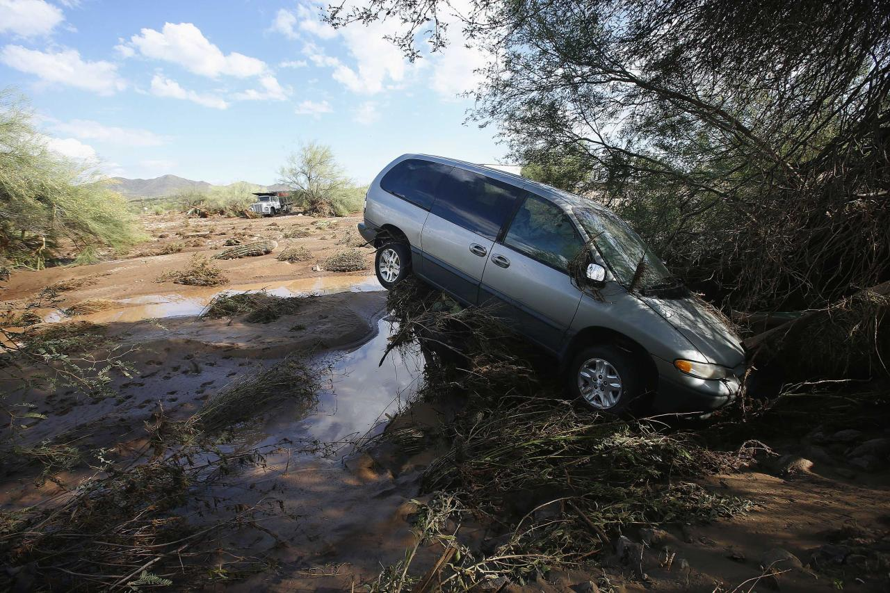 A vehicle sits atop debris where flash flood waters pushed it after rising waters overran Skunk Creek after strong storms moved through, Tuesday, Aug. 19, 2014, in New River, Ariz., just northwest of Phoenix. Heavy monsoon season rains that swept across Arizona on Tuesday led to dramatic rescues, road closures and flight delays as a series of fast-moving storms pummeled the state. (AP Photo/Ross D. Franklin)