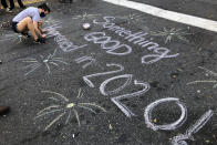 FILE - In this Nov. 7, 2020, file photo, Jolin Polasek draws a sign in chalk on a street in Harlem, New York to celebrate President-elect Joe Biden's win over President Donald Trump to become the 46th president of the United States. (AP Photo/Mark Lennihan, File)