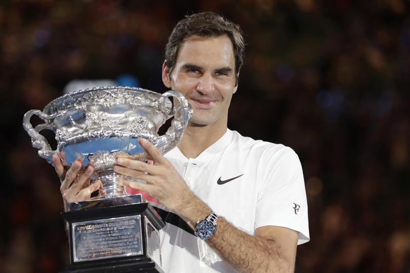 FILE - In this Jan. 28, 2018, file photo, Switzerland's Roger Federer holds his trophy after defeating Croatia's Marin Cilic in the men's singles final at the Australian Open tennis championships in Melbourne, Australia. Federer leads the list with 20 Grand Slam singles titles. Rafael Nadal has 19. Novak Djokovic has 16.(AP Photo/Dita Alangkara, File)