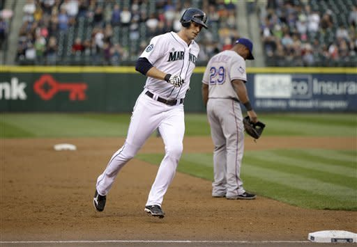 Seattle Mariners' Michael Saunders, left, heads to third base past Texas Rangers third baseman Adrian Beltre after Saunders hit a solo home run in the second inning of a baseball game, Saturday, Sept. 22, 2012, in Seattle. (AP Photo/Ted S. Warren)