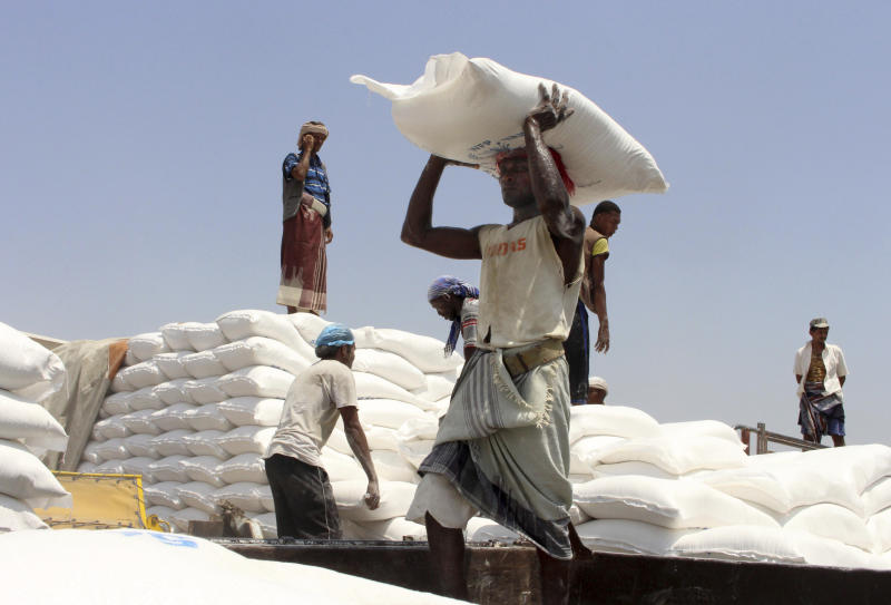 In this Sept. 21, 2018 photo, men deliver U.N. World Food Programme (WFP) aid in Aslam, Hajjah, Yemen. The United Nations and independent donors are rushing food to a desperate corner of northern Yemen where starving villagers were found to be living off leaves. But the hunger crisis continues to worsen. (AP Photo/Hammadi Issa)
