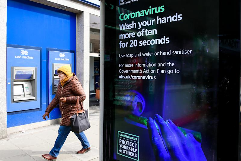 A woman walks past a Coronavirus public information campaign poster in London, which focuses on hand washing. Five coronavirus victims have died and 319 cases have tested positive for the virus. (Photo by Dinendra Haria / SOPA Images/Sipa USA)