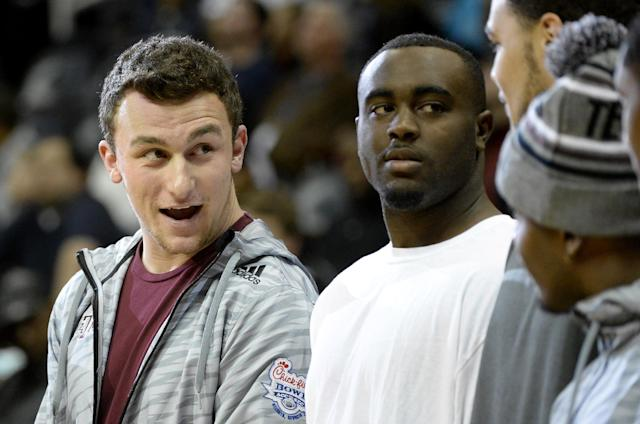 Texas A&M quarterback Johnny Manziel, left, joins his Aggies teammates as they participate in a halftime basketball skills competition against Duke as part of the Chick-fil-A Bowl NCAA college football week festivities during the Atlanta Hawks and Charlotte Bobcats NBA basketball game on Saturday, Dec. 28, 2013, in Atlanta. (AP Photo/David Tulis)