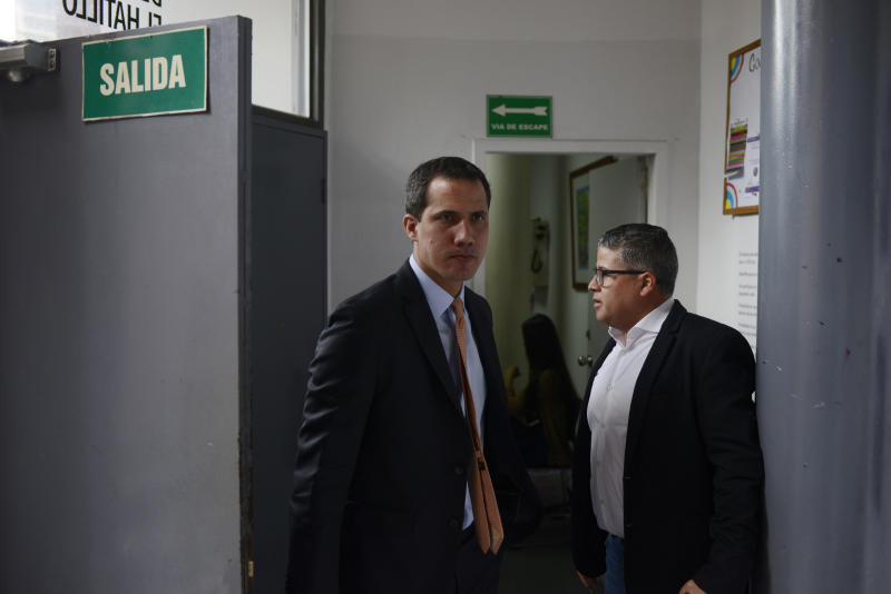 Opposition leader Juan Guaido arrives to a theater in the El Hatillo neighborhood where opposition lawmakers will hold a session after their vehicles were attacked by government supporters while driving to the National Assembly in downtown Caracas, Venezuela, Wednesday, Jan. 15, 2020. It's the second time this month that lawmakers have been barred from from the building that houses the only branch of government out of control of President Nicolás Maduro's socialist government. (AP Photo/Matias Delacroix)