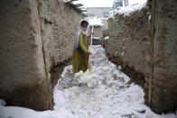 An internally displaced young Afghan woman cleans an alley outside her house on the outskirts of Kabul, Afghanistan, Sunday, Jan. 12, 2020. Kabul has been experiencing below freezing weather and snow. (AP Photo/Rahmat Gul)