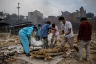 Pranav Mishra is helped by his relatives to place the body of his mother Mamta Mishra, who died from the coronavirus disease (COVID-19), on a pyre for her cremation at a crematorium ground in New Delhi