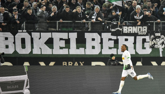 Moenchengladbach's Alassane Plea celebrates in front of supporters after he scored his second goal during the German Bundesliga soccer match between Borussia Moenchengladbach and FSV Mainz 05 in Moenchengladbach, Germany, Saturday, Jan. 25, 2020. (AP Photo/Martin Meissner)