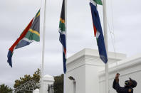 A policeman adjusts South African flags to half-mast outside parliament in Cape Town, South Africa, Wednesday, Nov. 25, 2020. South Africa declared five days of mourning starting today to remember those who have lost their lives to COVID-19 and gender-based violence.. (AP Photo/Nardus Engelbrecht)