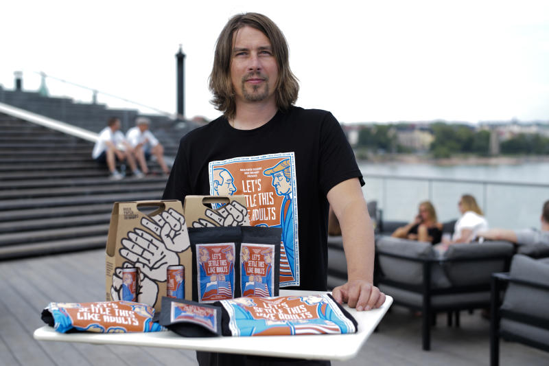 """Samuli Huuhtanen, CEO of Finnish beer brewery Rock Paper Scissors poses with beer, coffee and T- shirts, labeled with cartoon caricatures depicting Russian President Vladimir Putin and U.S President Donald Trump, during an interview with the Associated Press in Helsinki, Saturday, July 14, 2018. A small Finnish craft brewery is paying a humorous tribute to the July 16 Helsinki summit by a limited-edition lager beer depicting cartoon U.S. and Russian presidents on its label with a text urging Donald Trump and Vladimir Putin to settle things """"like adults"""". (AP Photo/Markus Schreiber)"""