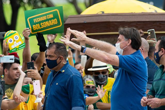 Brazilian President Jair Bolsonaro, right, has downplayed the severity of the coronavirus, even as cases and related deaths have skyrocketed across the country. (Andressa Anholete/Getty Images)