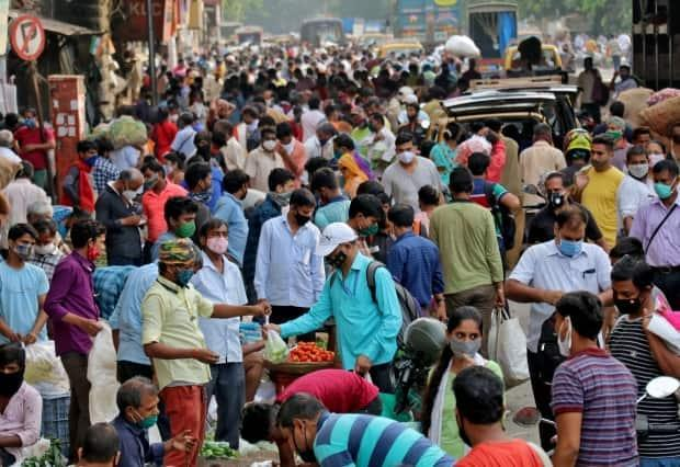 People shop at a crowded marketplace in Mumbai, India, on Wednesday while a new COVID-19 variant spreads like wildfire.