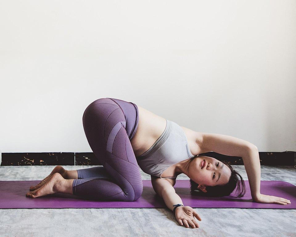 Yoga Poses for Digestion: Woman doing thread the needle yoga pose