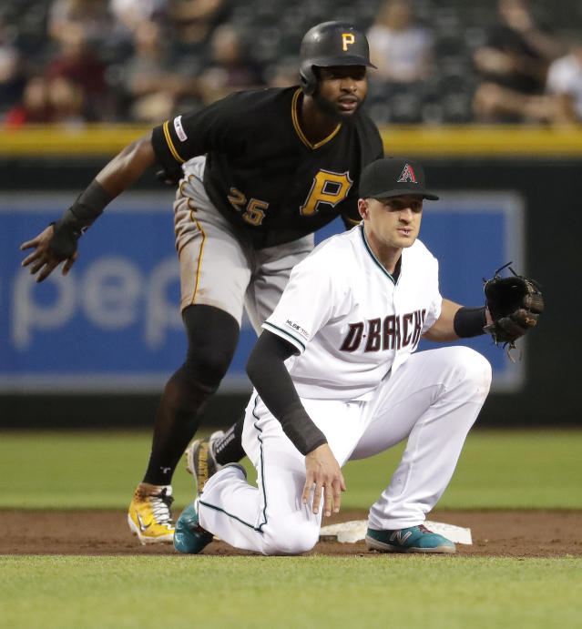 Pittsburgh Pirates' Gregory Polanco, left, and Arizona Diamondbacks' Nick Ahmed watch Josh Bell reach first safely after Polanco was forced out during the third inning of a baseball game Tuesday, May 14, 2019, in Phoenix. (AP Photo/Matt York)