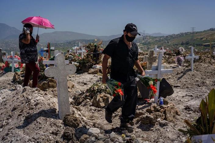 TIJUANA, BAJA CALIFORNIA -- MONDAY, APRIL 27, 2020: A relative arrives with flowers for the burial of Juan Velasco, who died of COVID-19 symptoms, at the Municipal Pantheon 13 cemetery, in Tijuana, Mexico, on April 27, 2020. (Marcus Yam / Los Angeles Times)