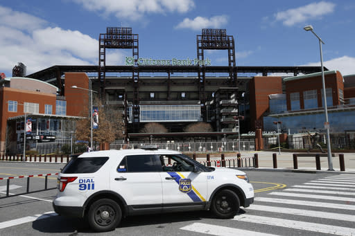 FILE - In this March 24, 2020, file photo, a Police vehicle blocks a street near Citizens Bank Park, home of the Philadelphia Phillies baseball team, in Philadelphia. On MLBs opening day, ballparks will be empty with the start of the season on hold because of the coronavirus pandemic. (AP Photo/Matt Slocum, File)