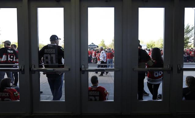 Chicago Blackhawks fans wait for a red carpet event on Medison Street in front of the United Center before an NHL hockey game between the Washington Capitals and the Blackhawks on Tuesday, Oct.1, 2013, in Chicago. The event was to launch the Blackhawks' 2013-2014 home opener on Tuesday. (AP Photo/Nam Y. Huh)