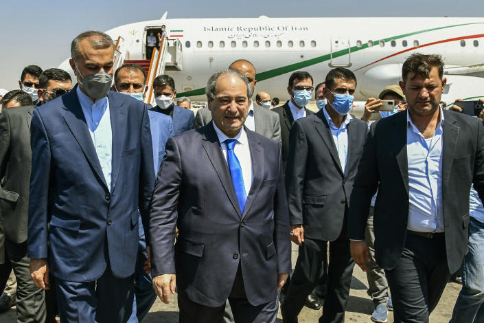 """In this photo released by the Syrian official news agency SANA, Syria's Foreign Minister Faisal Mekdad, center left, receives Iran's new Foreign Minister Hossein Amir-Abdollahian, left, in Damascus, Syria, Sunday Aug. 29, 2021. Mekdad said Sunday that the """"thunderous defeat"""" by the United States in Afghanistan will lead to similar defeats for American troops in Syria and other parts of the world. (SANA via AP)"""