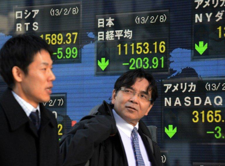 Businessmen pass a share prices board in Tokyo on February 8, 2013