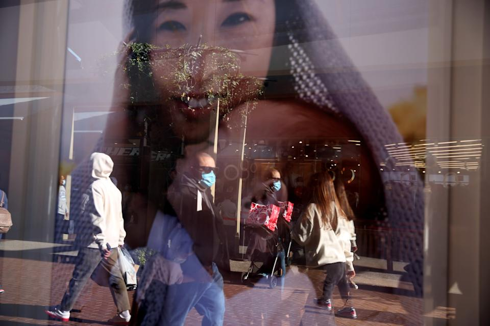 Shoppers at the Citadel Outlets are reflected in a window advertisement in Commerce.