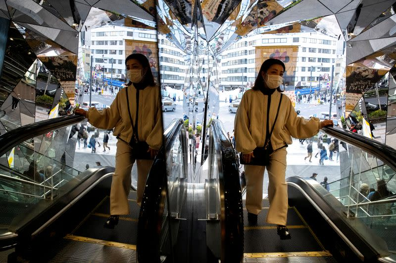 FILE PHOTO: A woman wearing a protective mask, following an outbreak of the coronavirus disease (COVID-19), is reflected in the mirror at a shopping mall in Tokyo