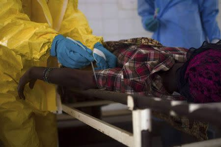 Medical staff take a blood sample from a suspected Ebola patient at the government hospital in Kenema