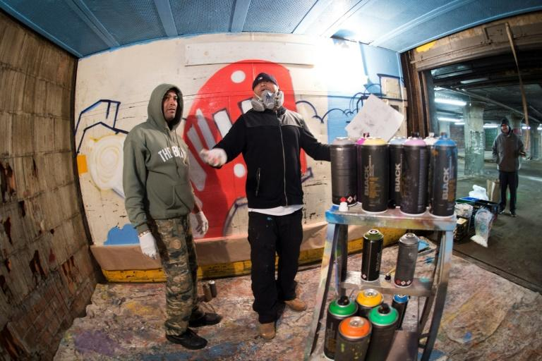 Bronx-based graffiti artist, turned professional muralist, BG183, works with one of his crew on a project in an old Bronx warehouse in New York