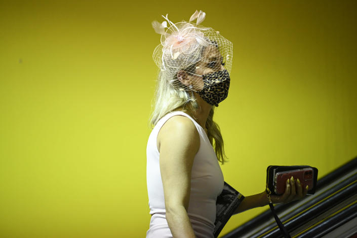 A woman wears a hat while taking an escalator ahead of the Preakness Stakes horse race at Pimlico Race Course, Saturday, May 15, 2021, in Baltimore. (AP Photo/Nick Wass)