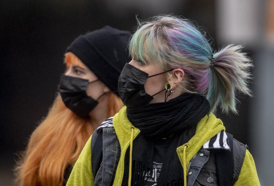 Two young women wearing face masks wait at a subway station in Frankfurt, Germany, Tuesday, Feb. 2, 2021. (AP Photo/Michael Probst)