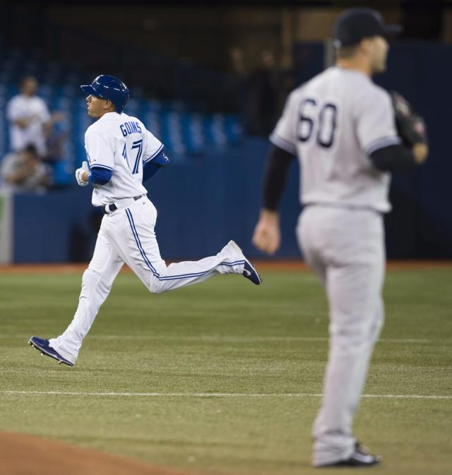 Toronto Blue Jays' Ryan Goins runs the bases on his home run past New York Yankees pitcher David Huff, right, during the fourth inning of MLB American League baseball action in Toronto Wednesday, Sept. 18, 2013. (AP Photo/The Canadian Press, Mark Blinch)
