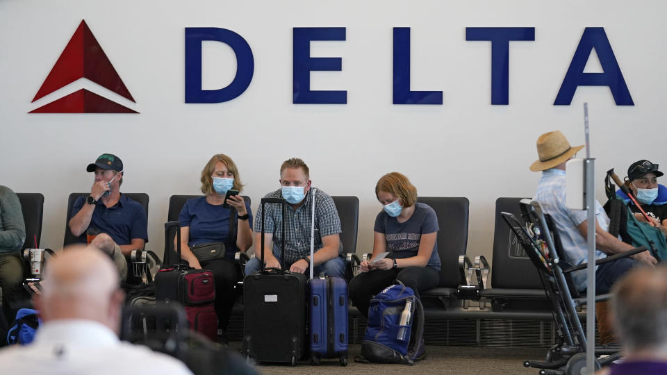 FILE - People sit under Delta sign at Salt Lake City International Airport on July 1, 2021, in Salt Lake City. Delta Air Lines won't force employees to get vaccinated, but it's going to make unvaccinated workers pay a $200 monthly charge. Delta said Wednesday, Aug. 25, 2021 that it will also require weekly testing for unvaccinated employees starting next month, although the airline says it'll pick up the cost of that testing. (AP Photo/Rick Bowmer, file)