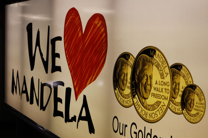 "A banner advertising gold coins with the image of former South African President Nelson Mandela, in Johannesburg, Sunday Dec. 9, 2012. South Africans prayed Sunday for the health of former President Nelson Mandela and anxiously awaited further word about the anti-apartheid leader after he was admitted to a military hospital. President Jacob Zuma visited Mandela Sunday morning at the hospital in Pretoria and found the frail 94-year-old to be ""comfortable and in good care,"" presidential spokesman Mac Maharaj said in a statement. Maharaj offered no other details about Mandela, nor what medical tests he had undergone since entering the hospital Saturday. (AP Photo/Denis Farrell)"