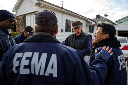 FILE PHOTO: Representatives from FEMA speak with a resident of the Staten Island borough neighborhood of New Dorp Beach about registering with the agency for financial assistance to help recover from the storm surge of Hurricane Sandy in New York, NY, U.S., November 15, 2012.  REUTERS/Lucas Jackson/File Photo