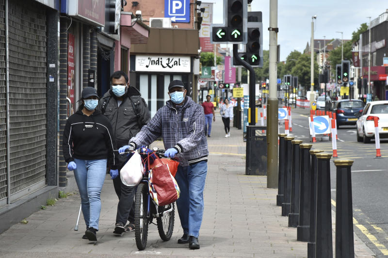 People wearing masks to protect against coronavirus, walk in Melton Road also known as the Golden Mile in Leicester, England, Tuesday June 30, 2020. The British government has reimposed lockdown restrictions in the English city of Leicester after a spike in coronavirus infections, including the closure of shops that don't sell essential goods and schools. (AP Photo/Rui Vieira)