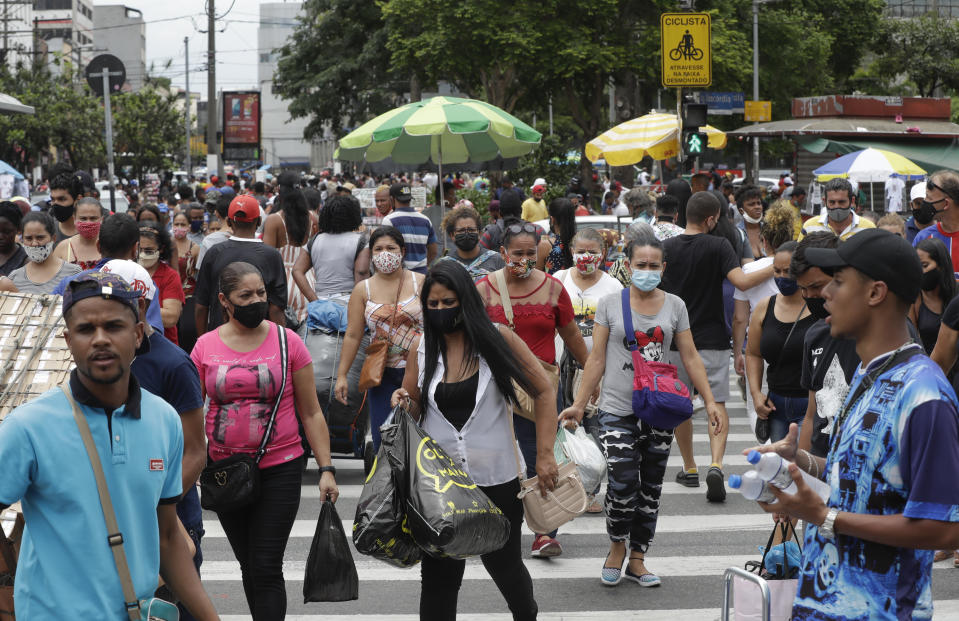 Shoppers cross a street in a downtown shopping district in Sao Paulo, Brazil, Tuesday, Dec. 15, 2020, amid the new coronavirus pandemic. (AP Photo/Andre Penner)