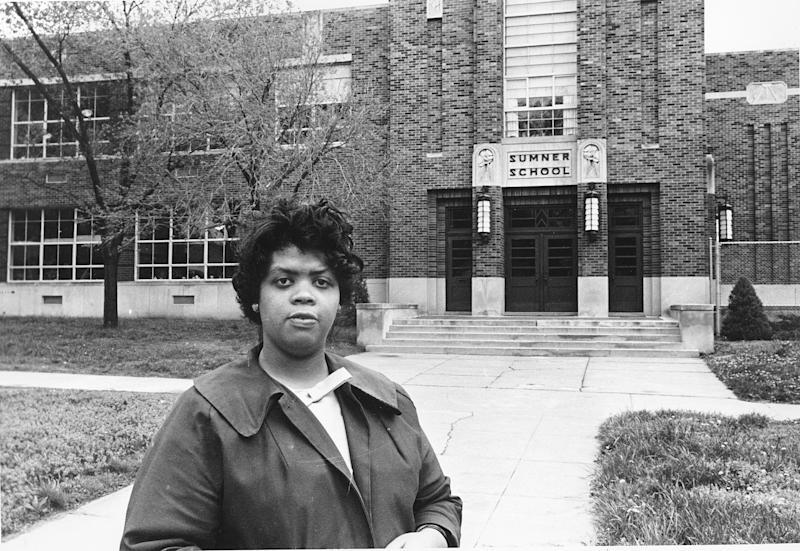 """FILE - This May 8, 1964 file photo shows Linda Brown Smith standing in front of the Sumner School in Topeka, Kansas. The refusal of the public school to admit Brown in 1951, then nine years old, because she is black, led to the Brown v. Board of Education of Topeka, Kansas. In 1954, the U.S. Supreme Court overruled the """"separate but equal"""" clause and mandated that schools nationwide must be desegregated. Saturday marks the 60th anniversary of the landmark Brown v. Board of Education decision. Many inequities in education still exist for black students and for Hispanics, a population that has grown exponentially since the 1954 ruling. (AP Photo, File)"""