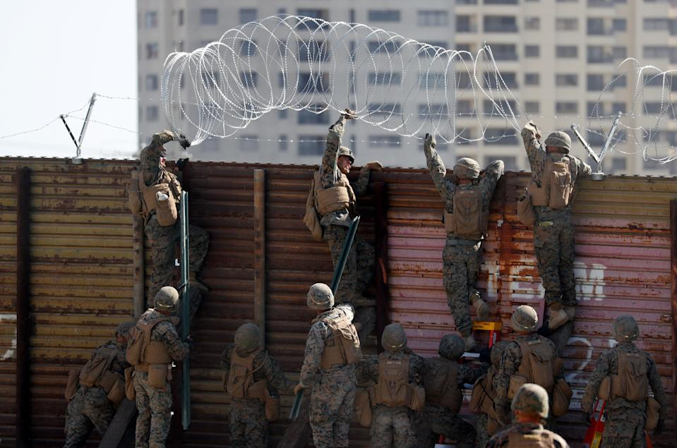 U.S. Marines instal concertina wire along the top of the primary border wall at the port of entry next to Tijuana in San Ysidro, San Diego, U.S., November 9, 2018. REUTERS/Mike Blake     TPX IMAGES OF THE DAY
