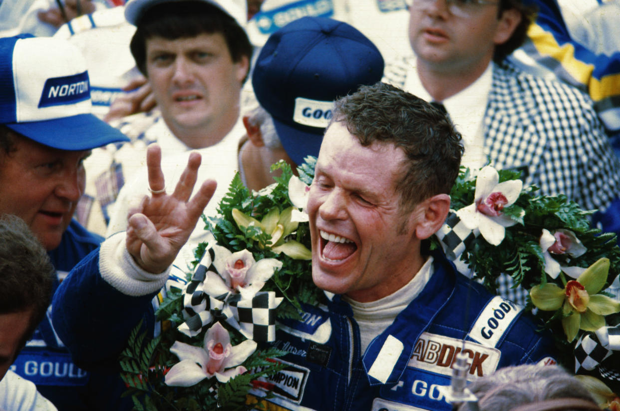 Race car driver Bobby Unser celebrates after winning the Indianapolis 500. He was later penalized one lap and stripped of the title.