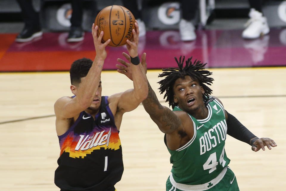 Boston Celtics forward Robert Williams III (44) reaches to knock the ball away from Phoenix Suns guard Devin Booker (1) during the second half of an NBA basketball game, Sunday, Feb. 7, 2021, in Phoenix. (AP Photo/Ralph Freso)